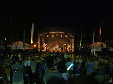 Image of a crowd of people standing behind a music stage at night time watching a woman on bass guitar on the left of the stage (as we view it), a man on drums in the middle of the stage, and another man on guitar on the right of the stage.