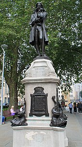 "Larger than lifesize bronze statue of man in period clothes, standing with one hand on a staff, the other raised to his chin. It is on a white stone pedestal with inscription Edward Colston Born 1636 Died 1721"", and bronze inscribed plaques below. Large bronze dolphins are on each corner of the base. It is in an urban setting with a large tree behind and above it."