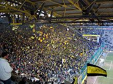 Vue depuis sous les toits d'une tribune à gauche pleine de supporters debout avec des drapeaux jaunes en plein match.