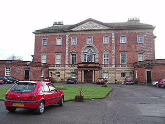 Tabley House - A large three-storey house, the bottom storey in stone, the upper storeys in brick, with a single-storey porch, over which is a Venetian window and a pediment