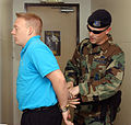 U.S. Air Force Senior Airman David Hill (right), Yokota Air Base Security Forces, handcuffs Airman 1st Class James Huntsman in a simulated burglary at the main chapel during an Operational Readiness Exercise 050724-F-EK722-017.jpg