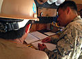 U.S. Navy Builder 1st Class Sergio S. Armas, with Naval Mobile Construction Battalion 3, inspects project log books to ensure Builder 3rd Class Micaela Tennant is keeping them up to date at Commander Fleet 130827-N-DM637-003.jpg