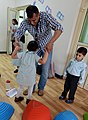 U.S. Navy Information Systems Technician 2nd Class Ariful Khan, top, assigned to Commander, Destroyer Squadron (DESRON) 50, dances with a little girl during a community relations event at the Regional Institute 131127-N-OU681-104.jpg