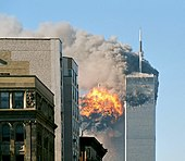 The twin towers are seen spewing black smoke and flames, particularly from the left of the two.