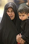 US Navy 030408-N-5362A-016 An Iraqi women waits with her son to receive food and water supplies at a humanitarian aid distribution site.jpg