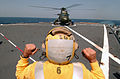 US Navy 040418-N-9849W-063 Steve Phifer, a civilian mariner assigned to the Military Sealift Command (MSC), stationed aboard USS Coronado (AGF 11), signals to a SH-3G Sea King helicopter to hold.jpg