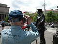 US Navy 040528-N-9909C-003 Stephen E. Kanyusik, a World War II veteran, takes some photographs of the Lone Sailor during the Navy's Battle of Midway Memorial Ceremony at the Navy Memorial in Washington, D.C.jpg