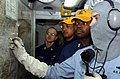 US Navy 041207-N-4953E-014 Interior Communications Electrician 2nd Class Shane Von Bergen, right, track damage control drills as Damage Control Training Team members evaluate the unit locker during a general quarters drill.jpg
