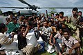 US Navy 050113-N-9885M-131 Victims of the Dec. 26 tsunami rush an MH-60S Knighthawk helicopter as crew members assigned to the Gunbearers of Helicopter Combat Support Squadron Eleven (HC-11) offload relief supplies.jpg