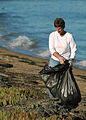 US Navy 051014-N-7286M-016 Photographer's Mate 1st Class Karen Elterman, stationed at Fleet Imaging Command Pacific, (FICP), places debris into a trash bag on board Naval Air Station North Island.jpg