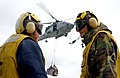 US Navy 060301-N-7571S-006 Sailors assigned aboard Nimitz-class aircraft carrier USS Theodore Roosevelt (CVN-71) communicate on the flight deck as an HH-60H Seahawk helicopter assigned to the.jpg