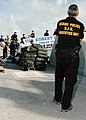 US Navy 070105-N-5240C-011 An officer with Miami's Special Investigation Section Narcotics Unit looks on as Sailors assigned to the guided missile frigate USS Robert G. Bradley (FFG 49), Coast Guardsmen, and agents from t.jpg