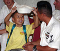 US Navy 070804-N-7109S-001 Store Keeper 2nd Class William Stewart, stationed aboard guided-missile frigate USS Jarrett (FFG 33), shares his white hat with a local student.jpg