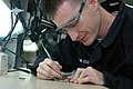 US Navy 071022-N-2757S-003 Aviation Electronics Technician 2nd Class Brian Van Essen removes the protective coating on a training circuit board to replace a chip so he can recertify as a soldering technician.jpg