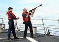 US Navy 080709-N-1082Z-005 Gunner's Mate 3rd Class Marcus W. Stapert, assisted by Operations Specialist 3rd Class Drew Hanna, shoots line across the bow of the guided-missile destroyer USS Ramage (DDG 61).jpg