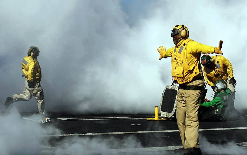 US Navy 081022-N-9928E-131 enior Chief Aviation Boatswain%27s Mate (Handling) Wilson Theodore, from New Orleans, directs an aircraft onto a catapult aboard the Nimitz-class aircraft carrier USS John C. Stennis (CVN 74).jpg