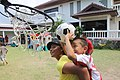 US Navy 100130-M-4593D-058 U.S. Army Sgt. Cassandra Wong, assigned to the 35th Combat Sustainment and Support Battalion, plays basketball with a child at the Mercy Center orphanage.jpg