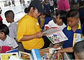 US Navy 110222-N-4773S-088 Machinist's Mate 3rd Class Mary Apostol reads to students from Nohong Charg Ngaw Elementary School during a community se.jpg