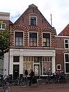 foto van Voorheen trapgevel van Haarlems type, bogen boven vensters op console rustend, engelen en leeuwenmaskers. Beneden verbouwd