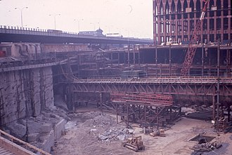 World Trade Center station (PATH) - Looking northwest. PATH eastbound tunnel F supported on a temporary trestle in foreground. Slurry wall with tie-backs can be seen on the left, and the frame of the North Tower in the background. Also note the since-removed West Side Elevated Highway, which ran above West Street (today's West Side Highway).