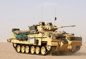 Warrior tracked armoured vehicle - FV510 Warrior in desert camouflage, with appliqué armour fitted, and infantry section's personal kit and other equipment outside.
