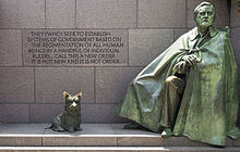 """A green statue of a man wrapped in a cloak alongside a statue of a Scottish Terrier."""