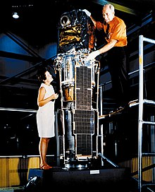 woman and man standing a satellite