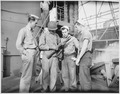 """Aboard a Coast Guard-manned transport..., a Negro Marine, Robert Stockman, goes over his carbine with Coast Guardsmen."" - NARA - 513195.tif"