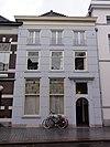 foto van Huis onder schilddak en met gebosseerd gepleisterde lijstgevel waarin empire-schuiframen