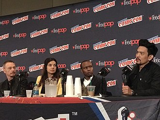 John Cho - Cho, right, promoting The Exorcist at the 2017 New York Comic Con. Beside him are his co-stars (left to right) Ben Daniels, Zuleikha Robinson, and Kurt Egyiawan.