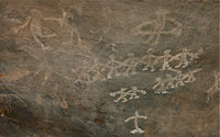 20 dancers with musician, some in group, few separate, a pre-historic rock cave painting near Bhopal India.jpg