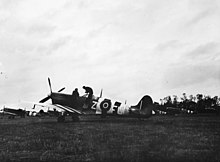 Black and white photo of World War II-era single-engined monoplane aircraft in a field. The fuselage and wings of the aircraft are marked with vertical black and white stripes.