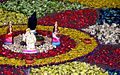 4 Radha Krishna Hindu deities at festival with traditional kolam floor art design.jpg