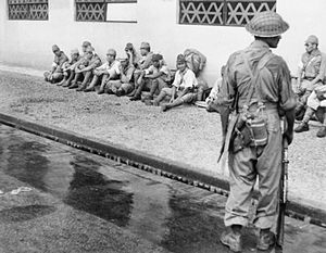 5th Infantry Division (India) - A soldier from the 5th Division stands guard over Japanese prisoners who surrendered during the liberation of Singapore. September 1945.
