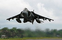 Grey jet aircraft executing a vertical takeoff with line of tropical trees serving as backdrop. Under each wing is an external fuel tank