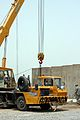 A crane operator removes barriers from Joint Security Station (JSS) Falcon, Iraq, as U.S. Soldiers with 5th Squadron, 4th Cavalry Regiment (Long Knife), 2nd Advise and Assist Brigade, 1st Infantry Division 110720-A-BR577-021.jpg