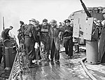 A wounded soldier being helped aboard the cruiser HMS FROBISHER off the Normandy coast, 6 June 1944. A24104.jpg