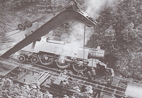 The derailed locomotive on its side.