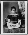 African American girl, half-length portrait, standing at table with illustrated book, facing slightly right LCCN99472198.tif