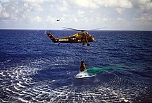 "A green helicopter hovers low over the water, with the Mercury capsule suspended below. The helicopter has ""Marines"" written on it, and the number ""44"""