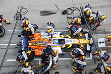 mechanics change tyres and refuel a race car