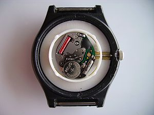 Quartz clock - Basic quartz wristwatch movement. Bottom right quartz crystal oscillator, left button cell watch battery. Top right oscillator counter, top left the coil of the stepper motor that powers the watch hands.