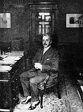 homem no final da meia-idade, cabeça cheia de cabelos grisalhos, bigode, sentado em uma mesa