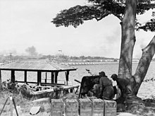 Men crouch behind the shield of an artillery gun beneath a tree overlooking a body of water