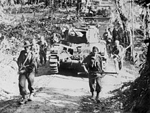 Soldiers in combat equipment carrying rifles advance along a dirt road in front of a tank