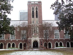 A wide, red brick building with a tower in the center and grey concrete archways spaced along the length of the building