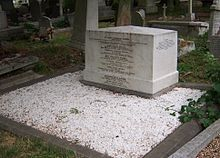 A cubical white marble work of masonry, approximately three feet wide, 18 inches deep and two foot high, inscribed with names of members of the Brunel family, surrounded by marble chippings
