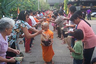 Culture of Thailand - Buddhist novices receiving joss sticks.
