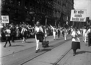 "Occupation of the Ruhr - Protests by gymnasts from the Ruhr at the 1923 Munich Gymnastics Festival (The sign on the left reads ""The Ruhr remains German""; the sign on the right reads ""We never want to be vassals"".)"