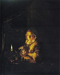 Young woman winding up a watch by candlelight